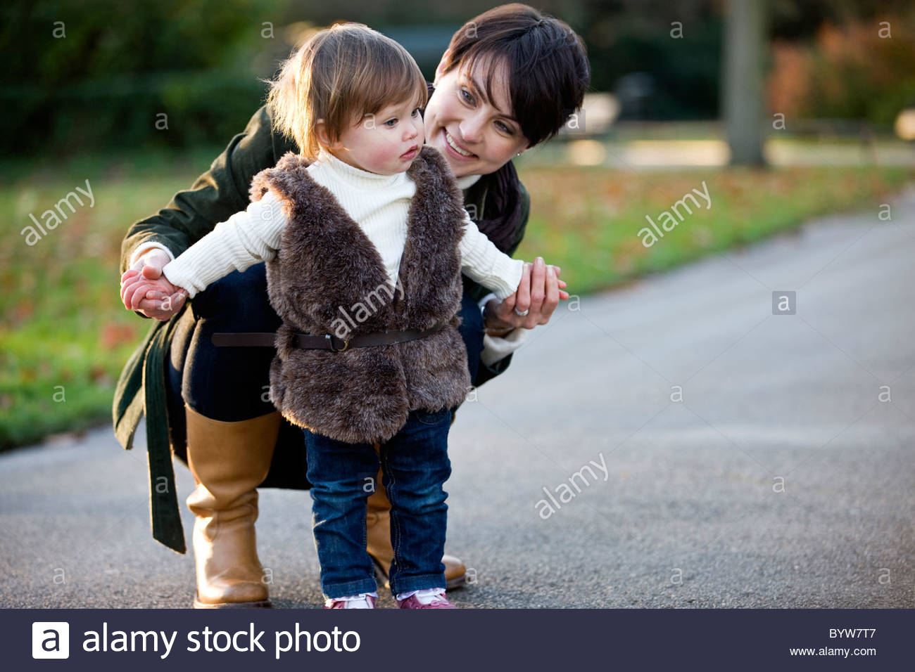 A mother helping her daughter stand in the park - Stock Image