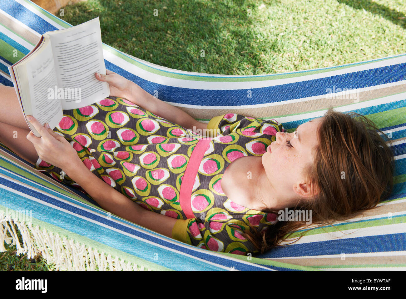 Girl reading a book in a hammock - Stock Image