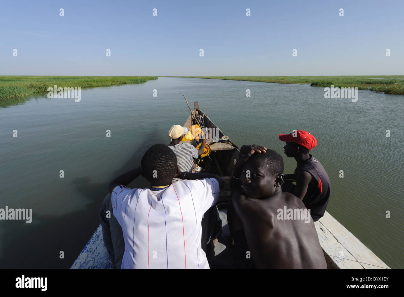 Passengers and steersman sitting on the front side of a pinasse, cruising the Niger Inland Delta. Mali. - Stock Image