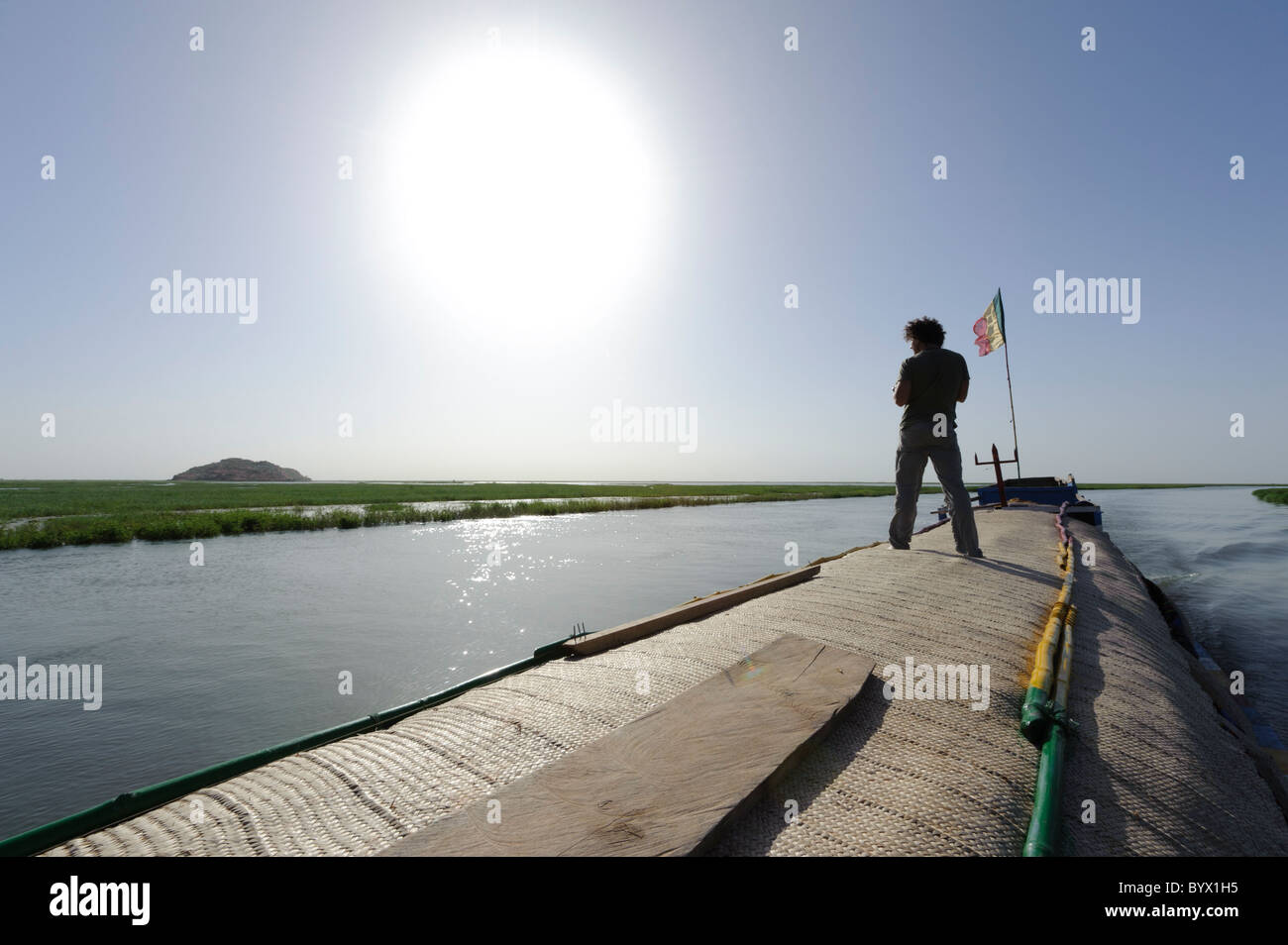 Western tourist standing on the roof of a pinasse during a boattrip on the Niger Inland Delta and Lake Debo. Mali. - Stock Image