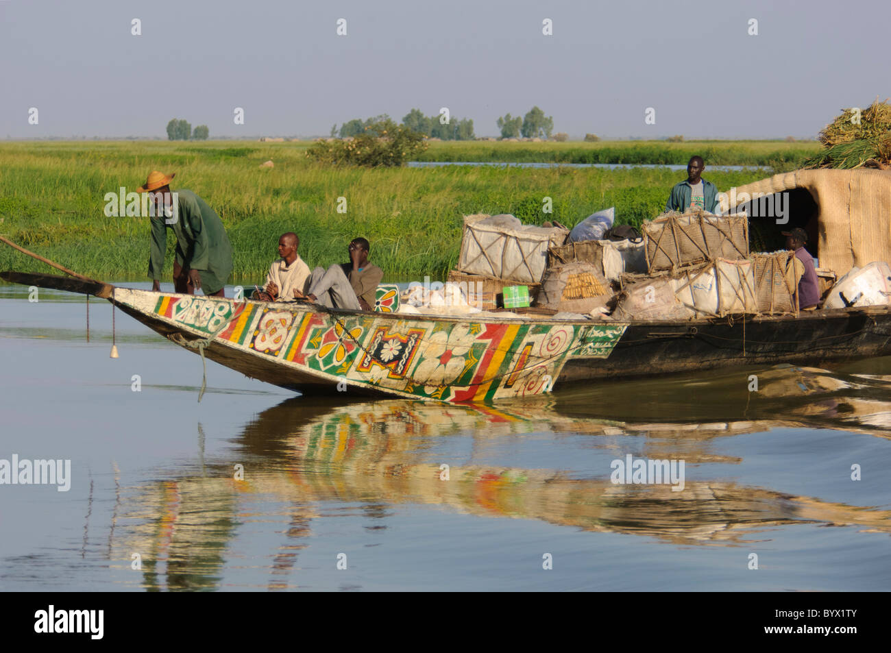 Passengers and steersman sitting on the front side of a transportation pinasse, cruising the Niger Inland Delta. - Stock Image