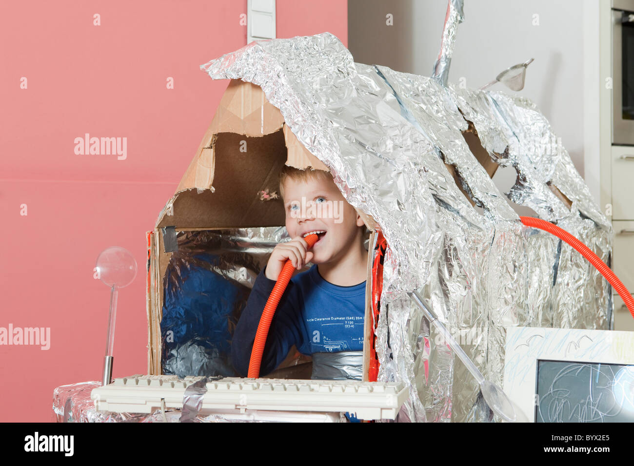 Boy in self constructed house, smiling - Stock Image