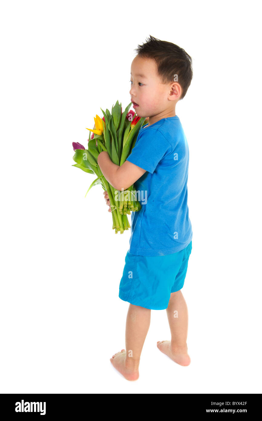 Asian boy with light handicap and a colorful bouquet tulips  - Stock Image