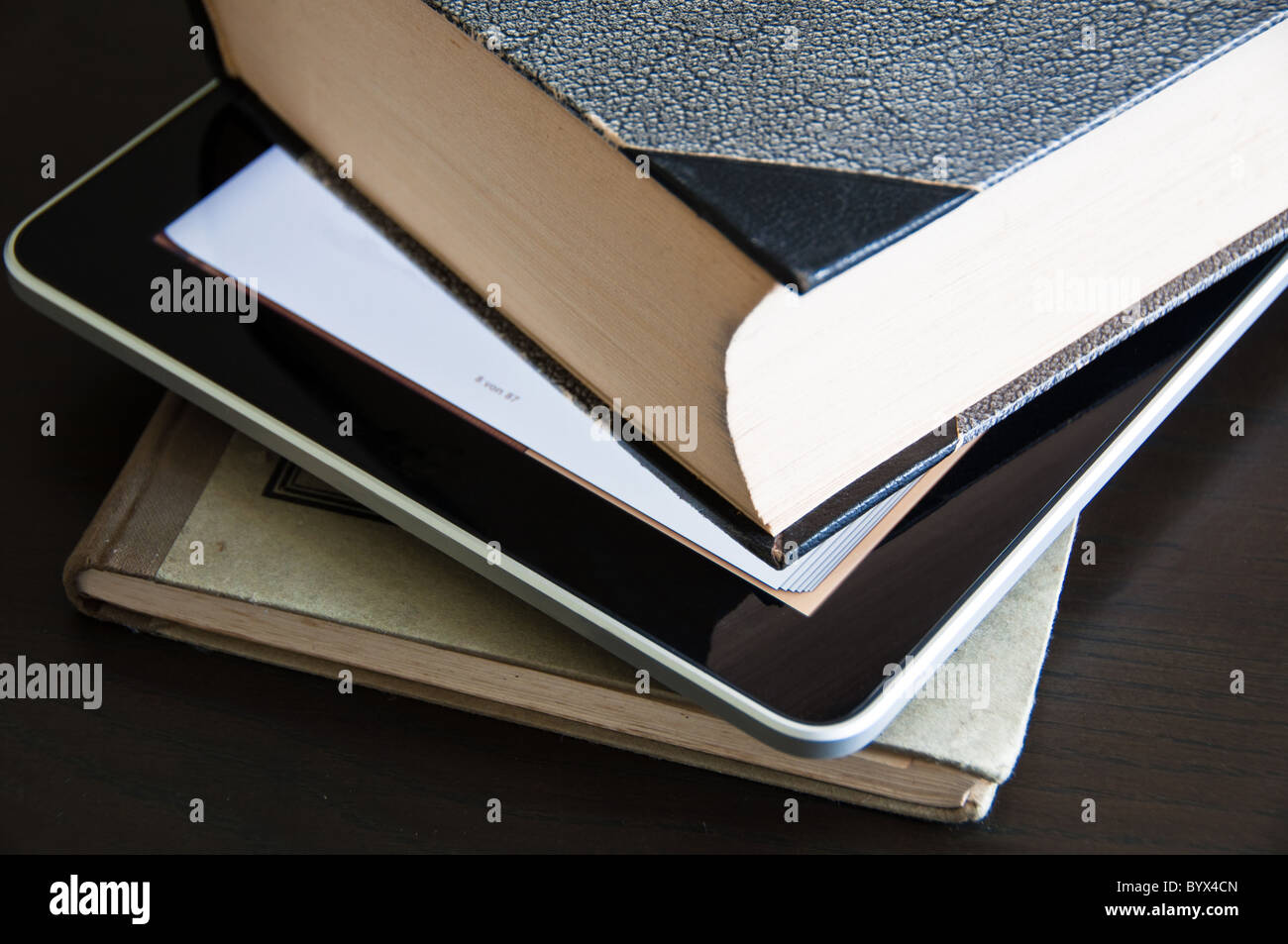 Close-up of two old books with modern digital tablet (eBook reader) in between - Stock Image