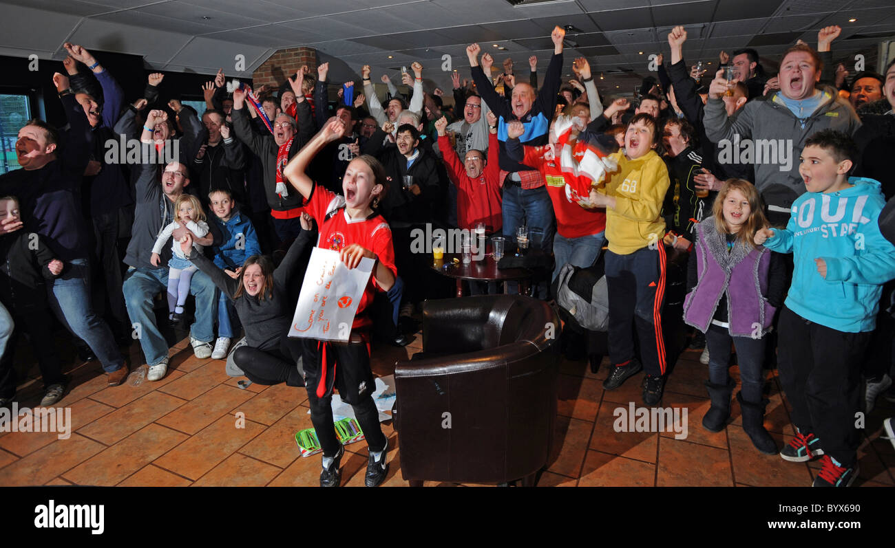 Crawley Town football fans celebrate wildly as their team is pulled out to play Manchester United in the 5th round - Stock Image