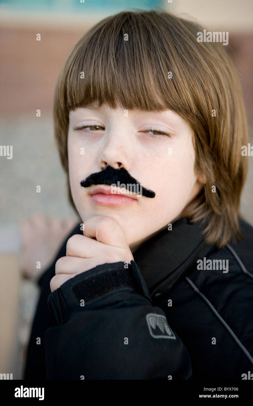 An eight year old boy wearing a pretend moustache with hand on chin, acting like an adult man in deep thought. - Stock Image