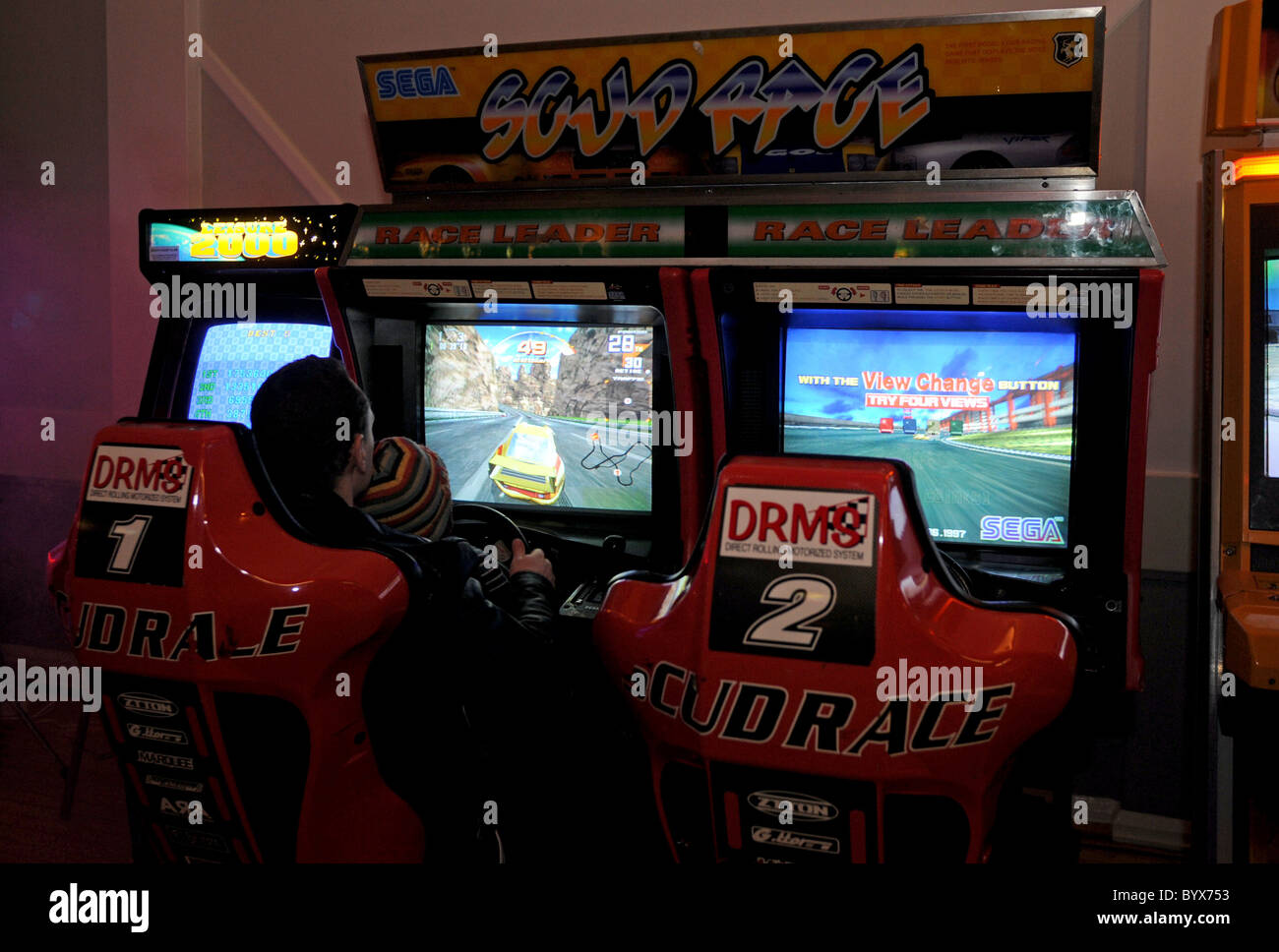 A father and son play video games in an arcade - Stock Image
