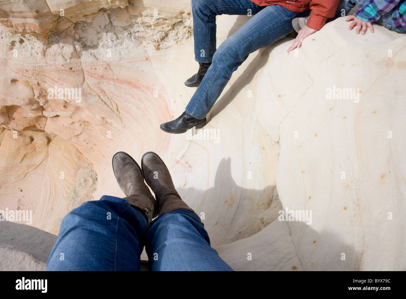 women wearing boots resting on sandstone, high desert of New Mexico, USA - Stock Image