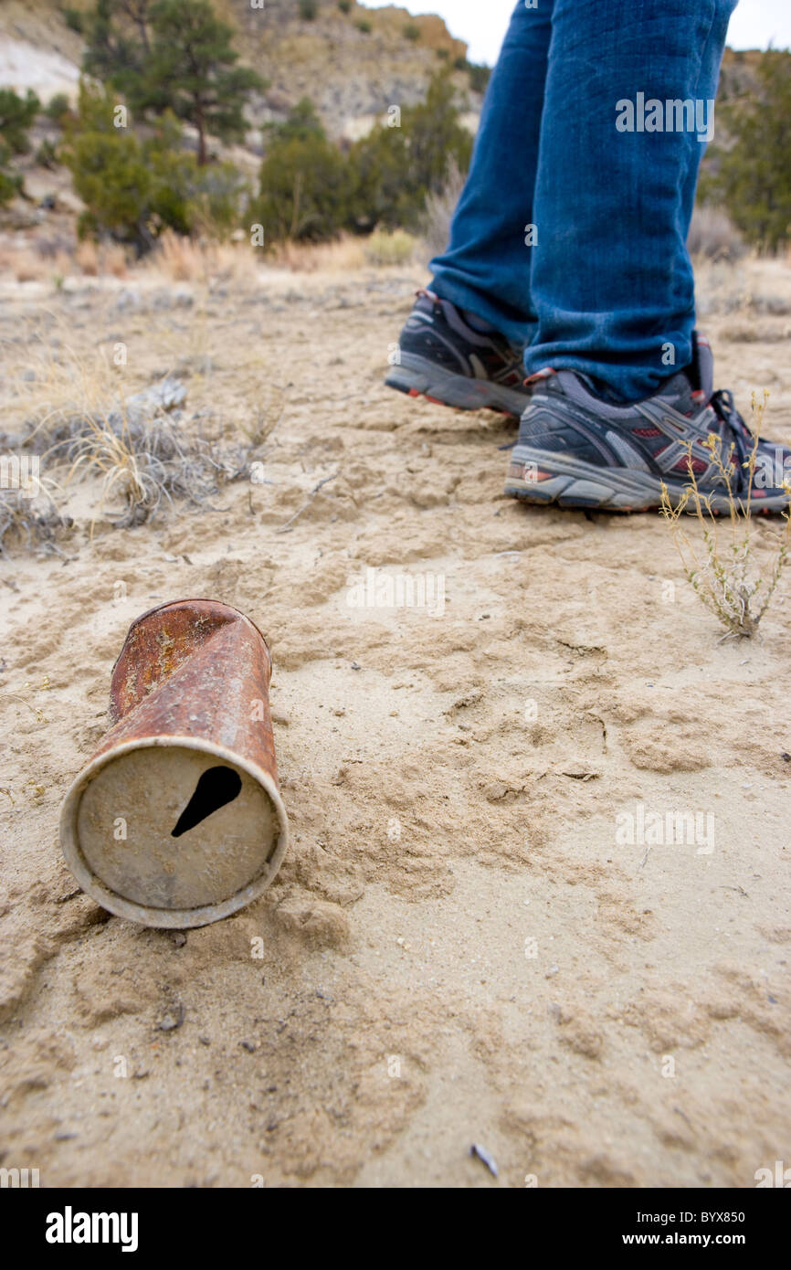 old rusted aluminum can next to a boy's feet, desert of Southwestern USA - Stock Image
