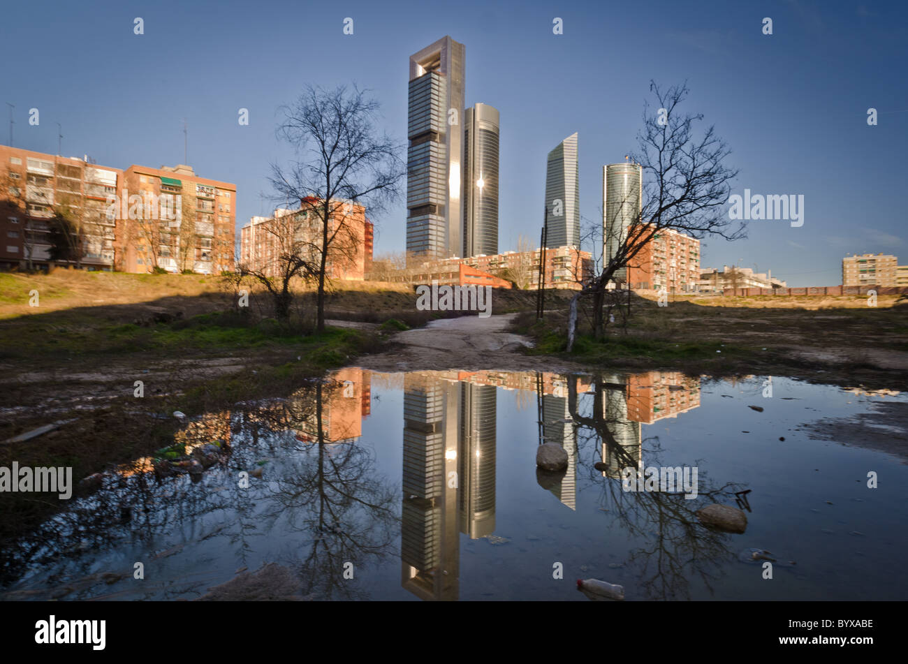 Cuatro Torres Business Area (CTBA) (Spanish for Four Towers Business Area) next to poor housing and wasteland - Stock Image