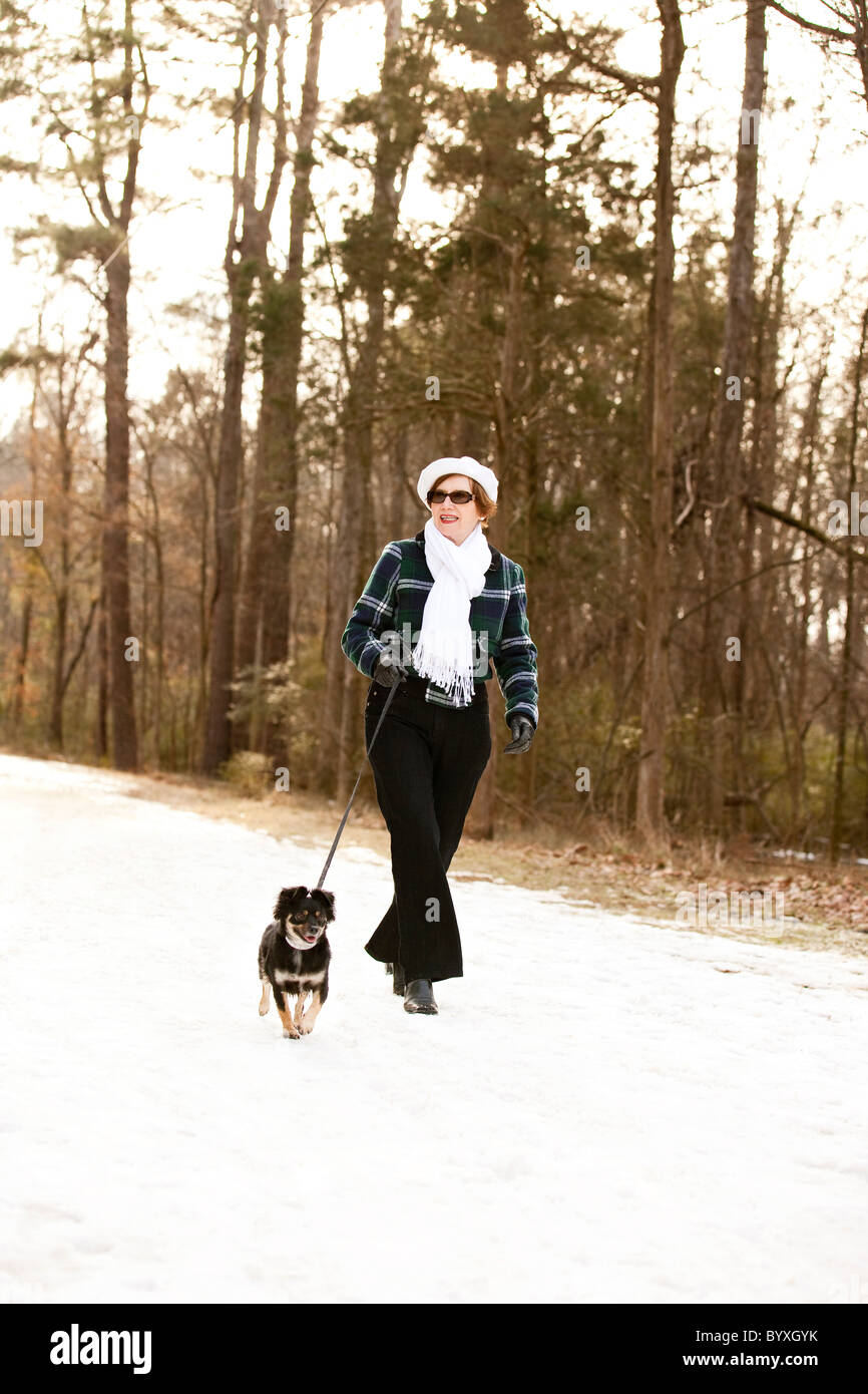 woman walking her dog in snow - Stock Image