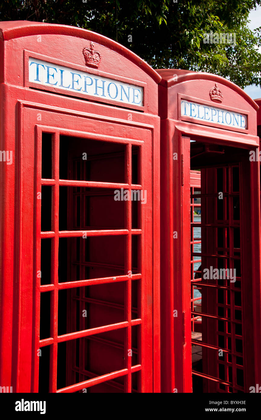 Two red telephone kiosk boxes side by side, closeup details, no identifiable background - Stock Image