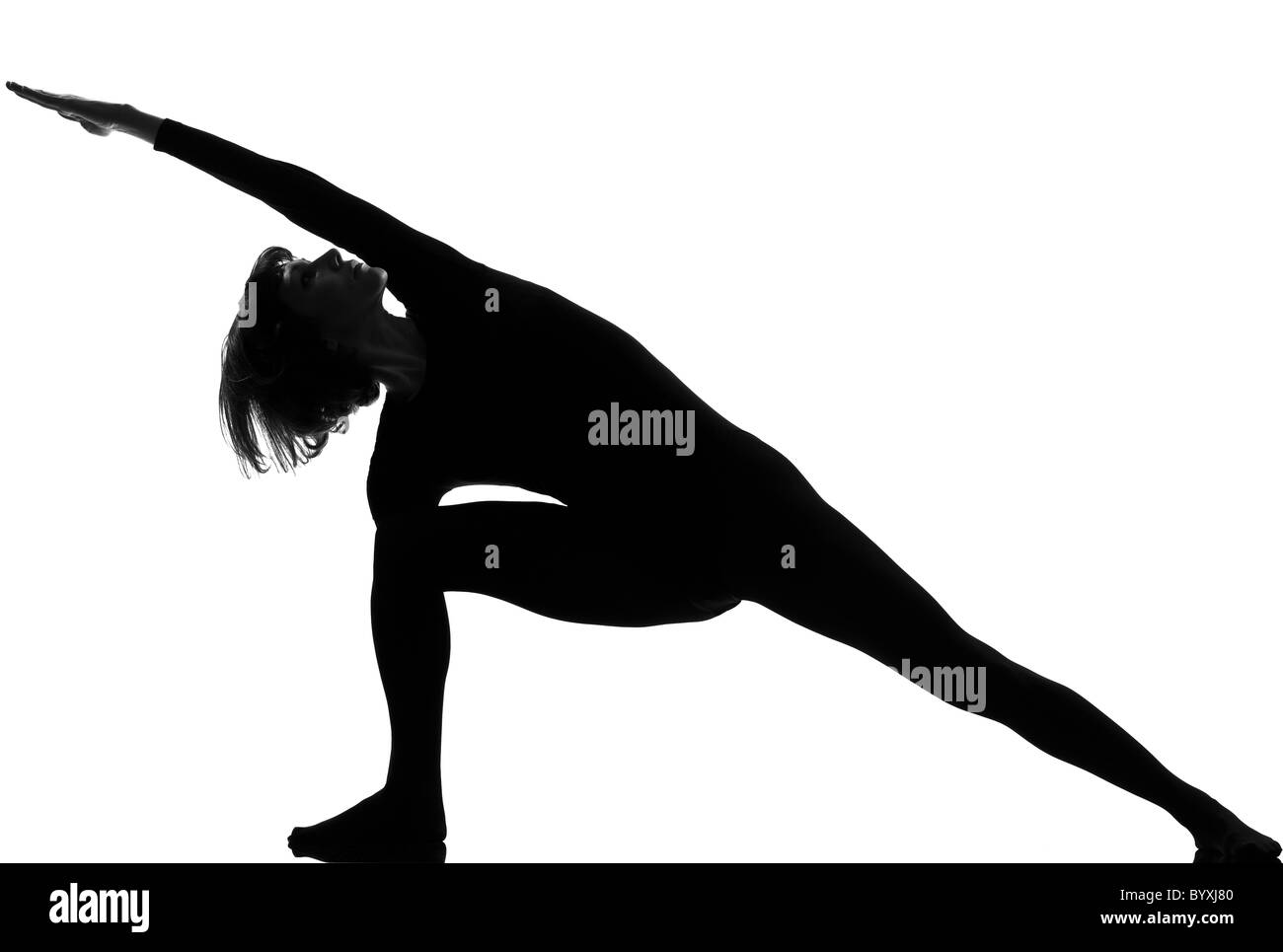 woman yoga posture Extended Side Angle Pose position in silouhette on studio white background - Stock Image