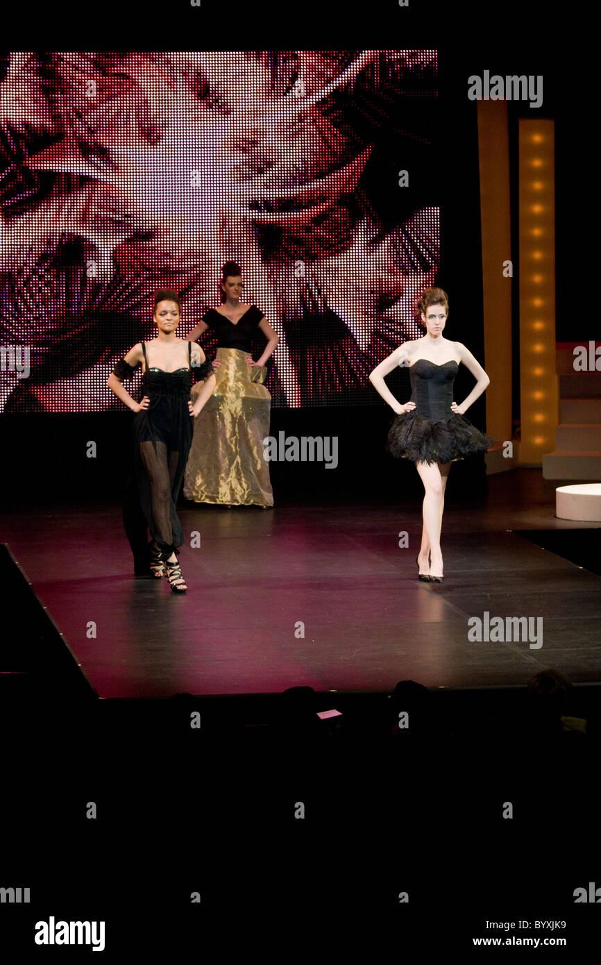 two female models walking posing runway - Stock Image