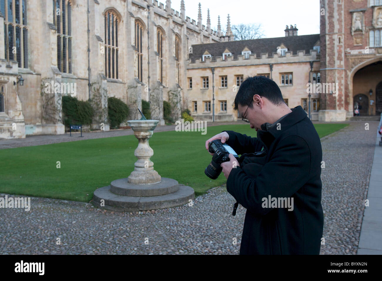 Tourist looking at the back of his digital camera in the Great Court of Trinity College Cambridge - Stock Image