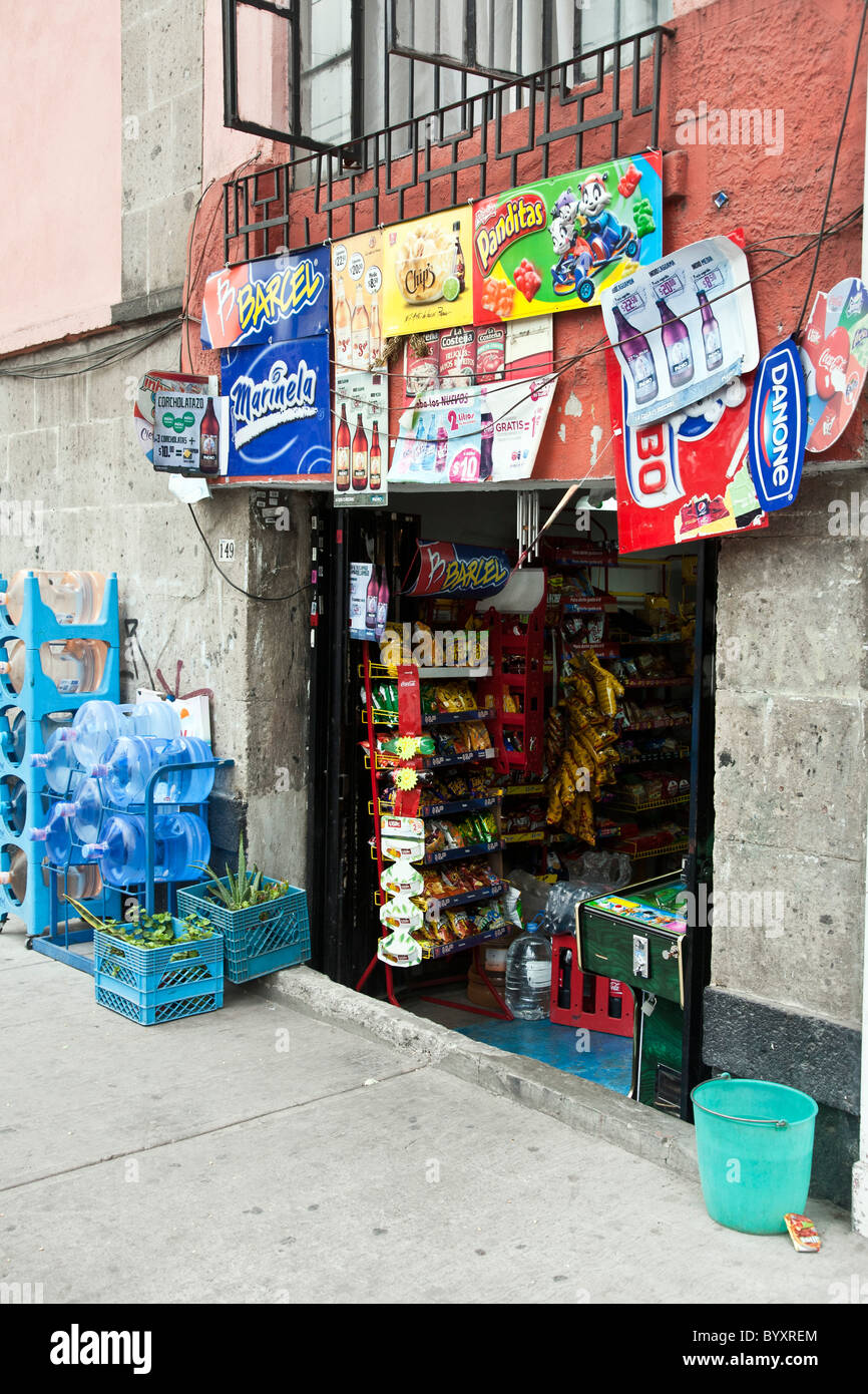 hole in the wall bodega selling junk food plastered with advertising signs for Mexican sodas snacks Roma district - Stock Image