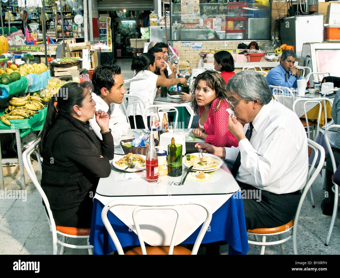 Mexican diners enjoy plates of hearty simple food in bright colorful restaurant area  Medellin market Roma district - Stock Image