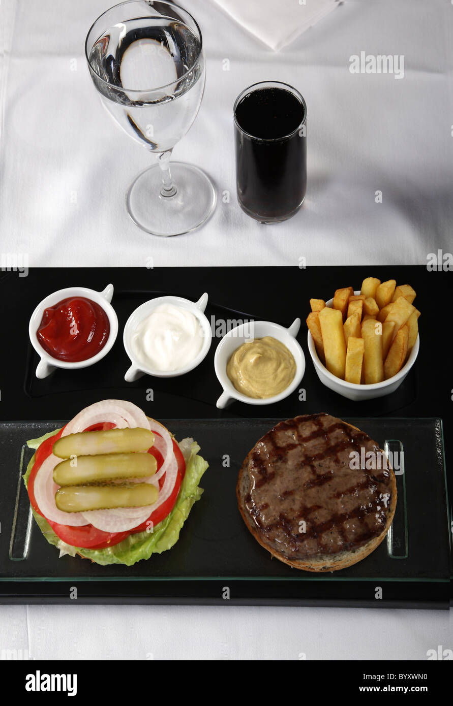 Burger and french fries served on a classic table Stock Photo