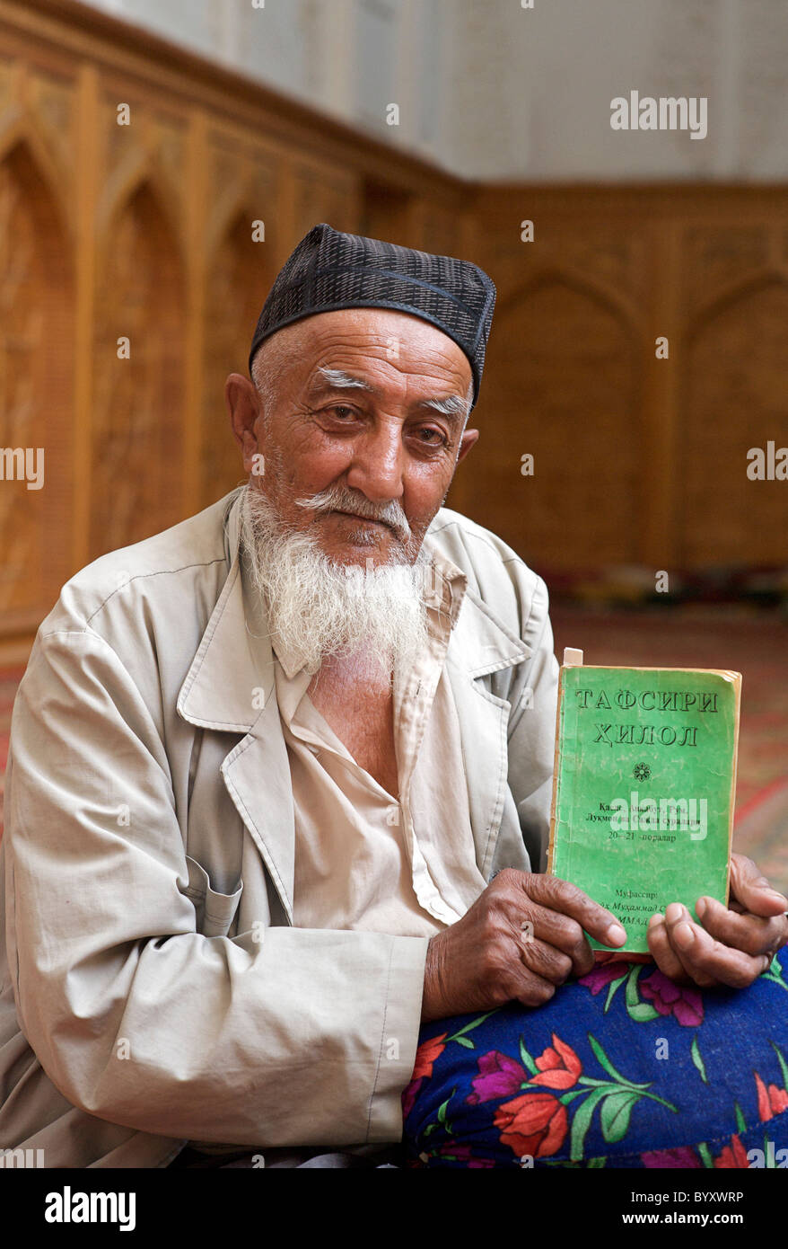 Portrait of  elderly muslim man. The Muezzin at a mosque with a Koran in Cyrillic script, Khiva, Uzbekistan. RELEASED - Stock Image