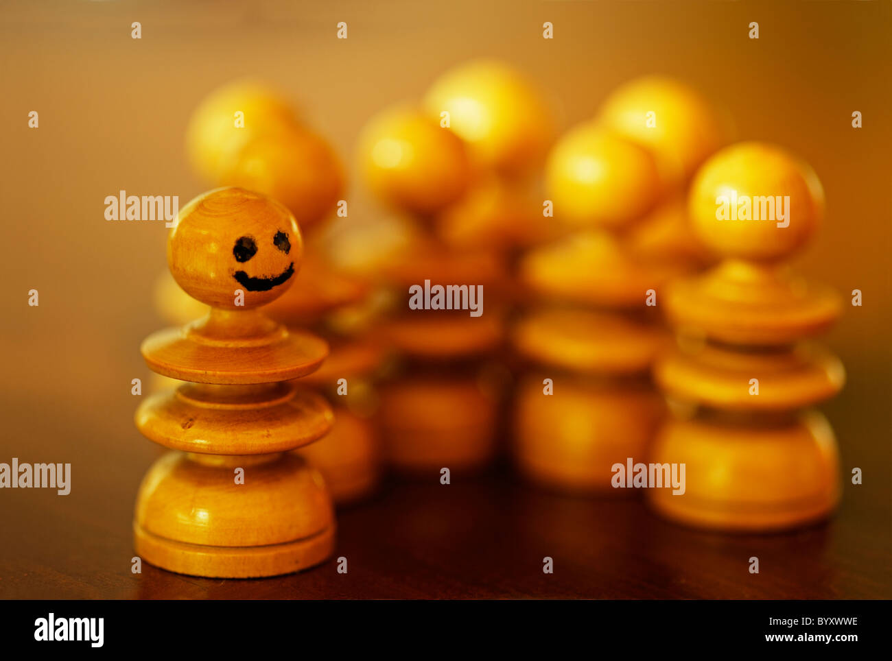 Happy pawn stands out from the crowd. - Stock Image