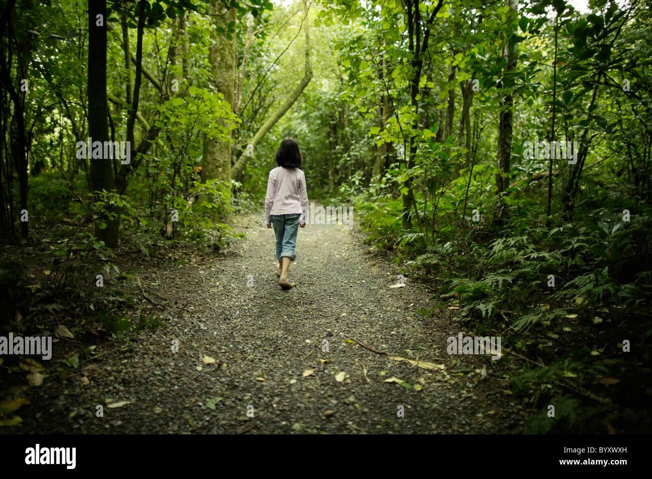 Girl walks along woodland path, New Zealand. - Stock Image