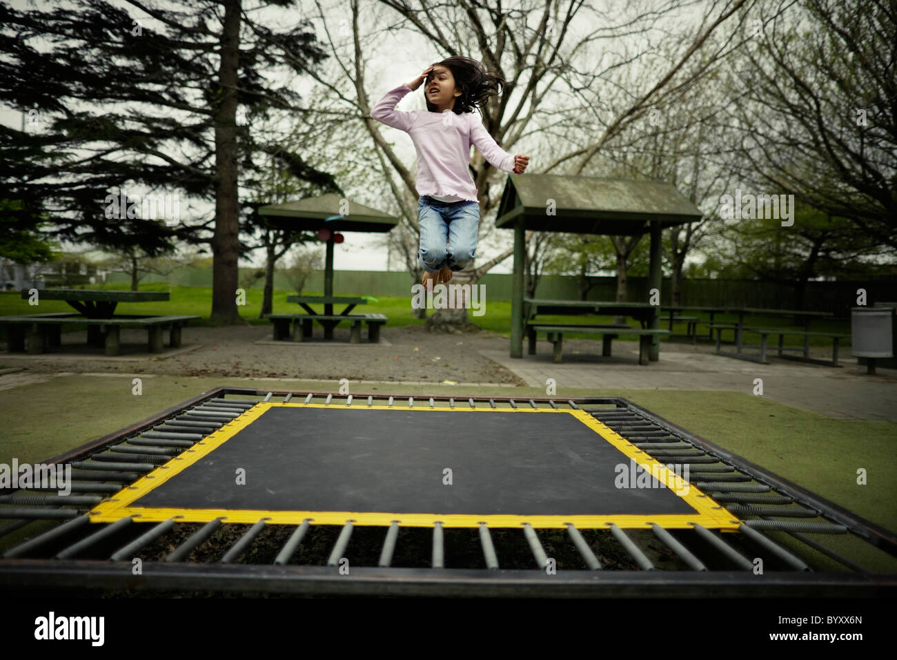 Girl bouncing on trampoline in public park, New Zealand. - Stock Image