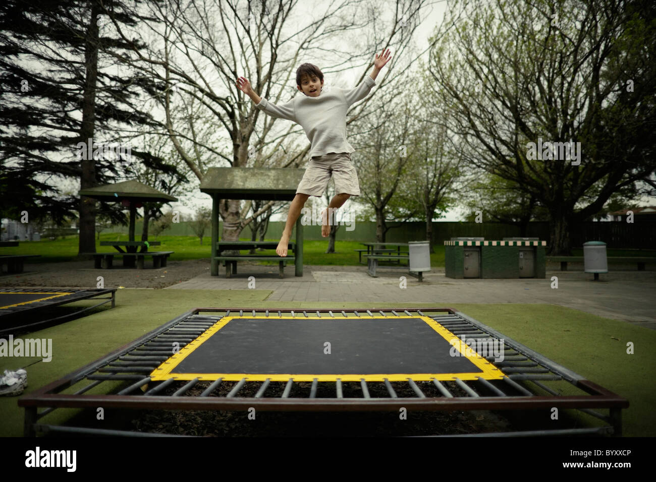 Boy bounces on trampoline in public play ground, New Zealand. - Stock Image