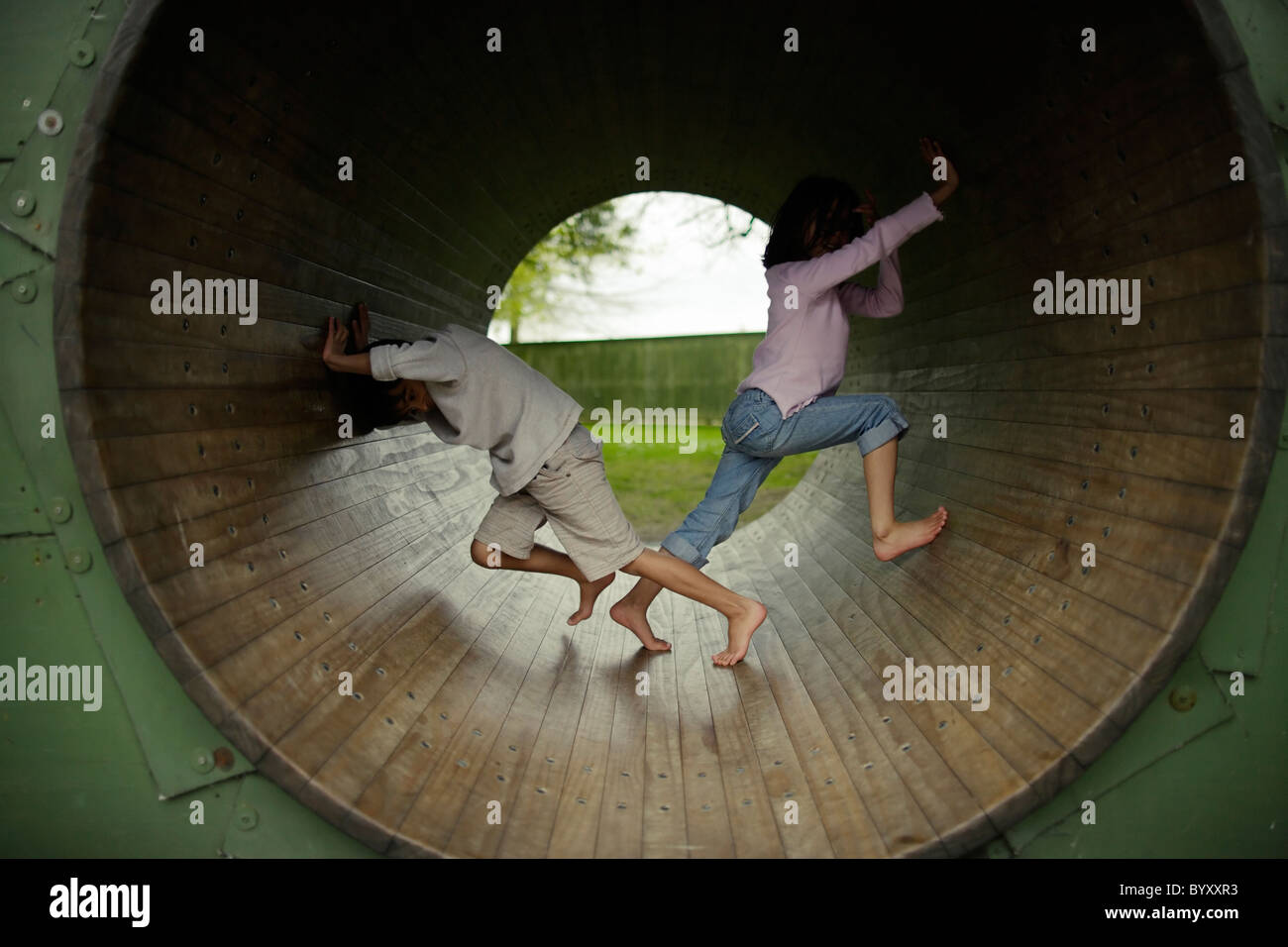 Not Teamwork. Boy and girl try to turn playground hamster wheel in opposite directions. Public playground, New Zealand. - Stock Image
