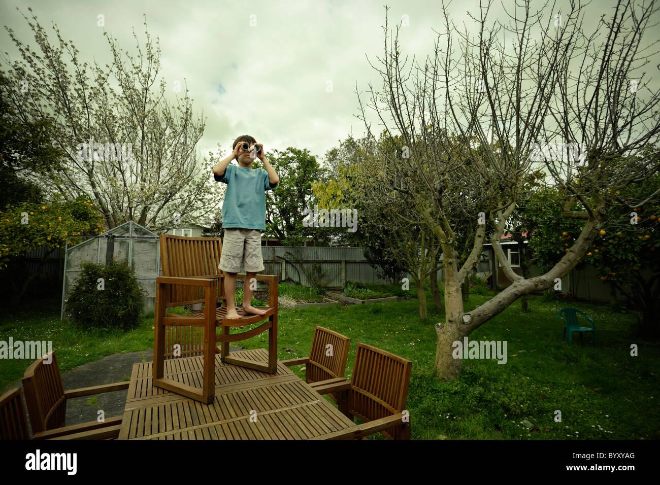Boy stand on chair on garden table, using cardboard tubes as pretend binoculars. Stock Photo