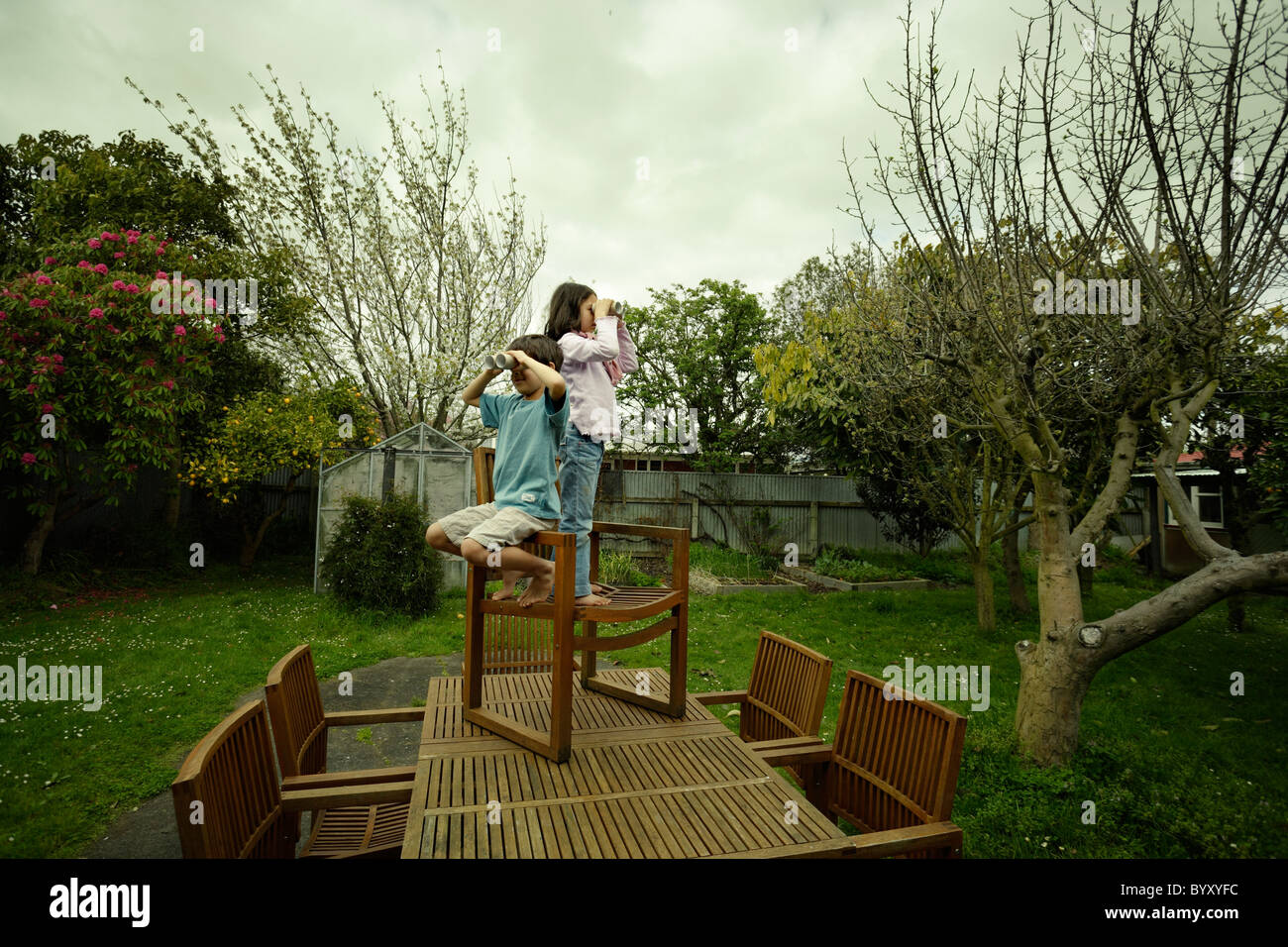 Boy and girl stand on chair on garden table, using cardboard tubes as pretend binoculars. Stock Photo