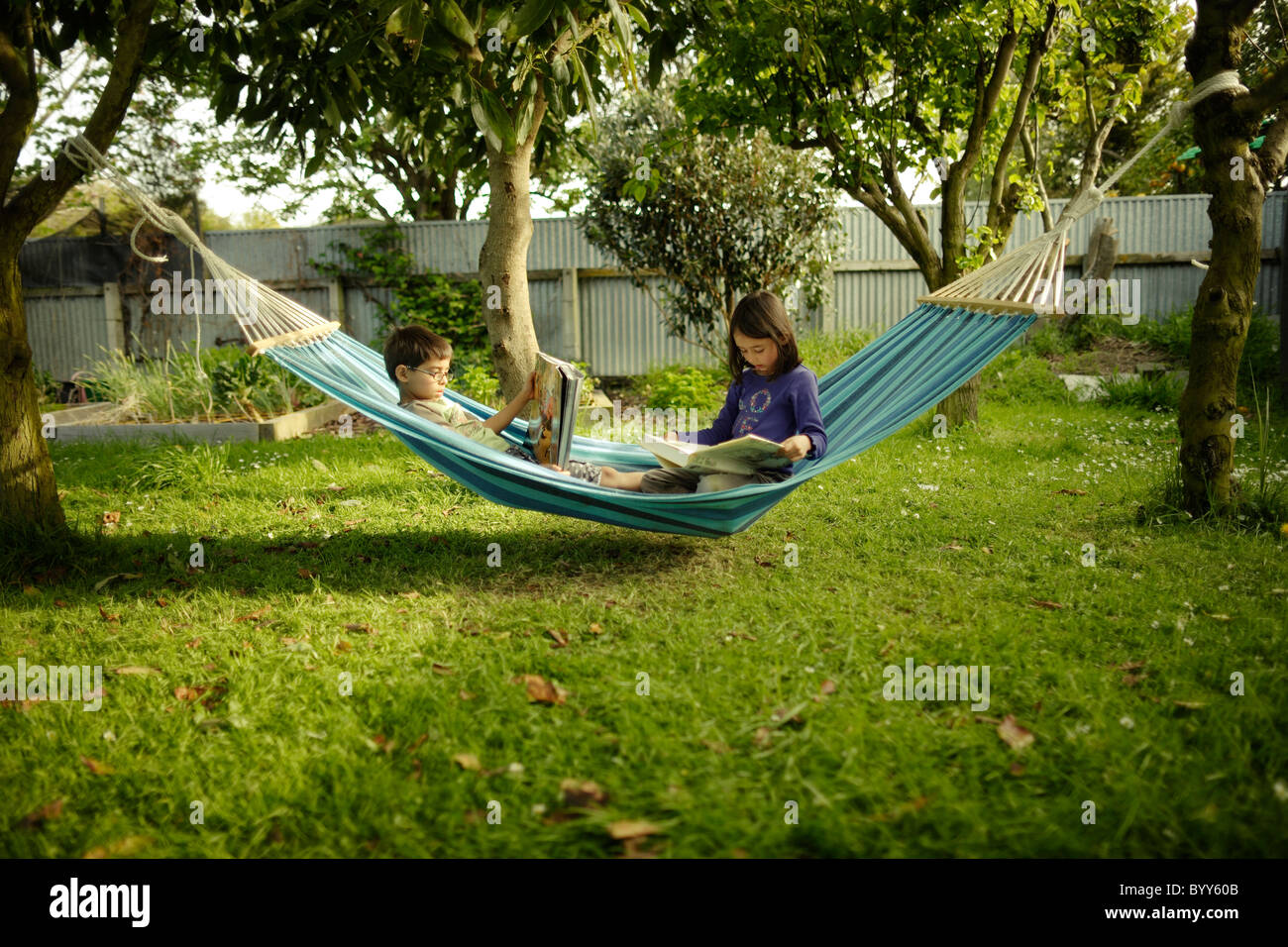 Boy and girl share hammock to read books on warm summer evening - Stock Image