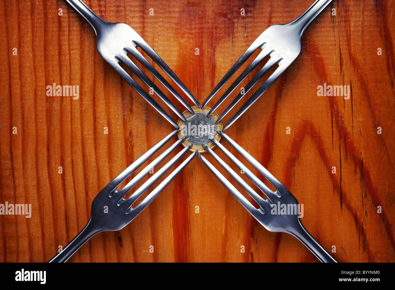Four forks fighting over one euro coin , financial crisis competition ,wood background - Stock Image