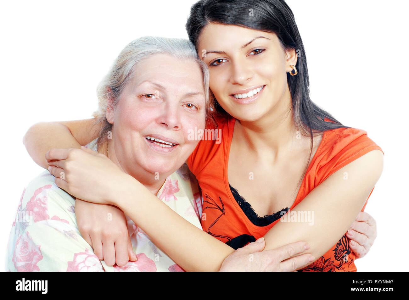 Smiling grandmother and granddaughter embracing,white background ,horizontal - Stock Image