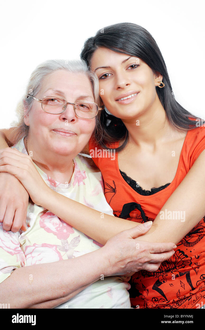 Smiling grandmother and granddaughter embracing,white background ,vertical - Stock Image