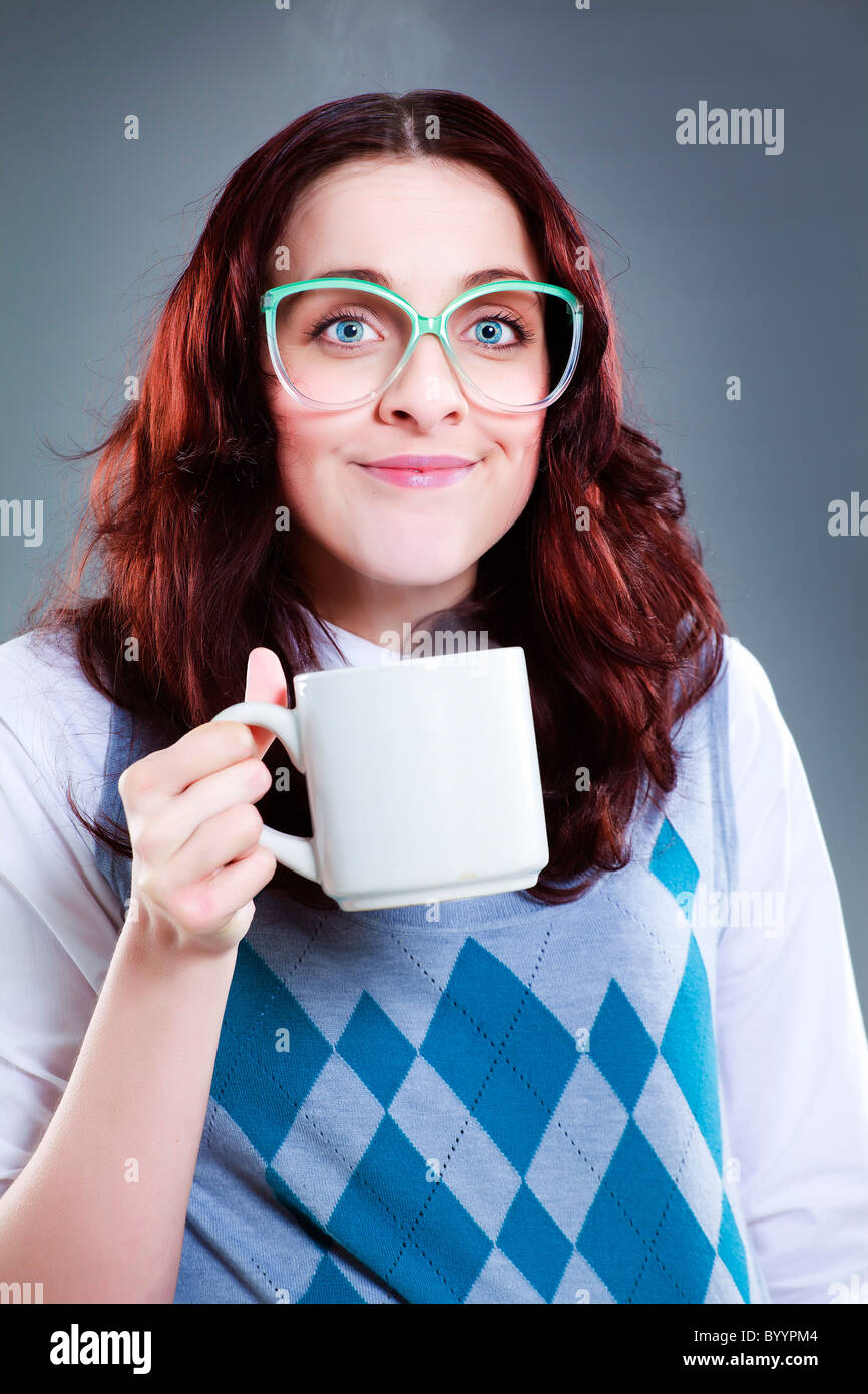 Simple geeky woman holding a plain white mug - Stock Image