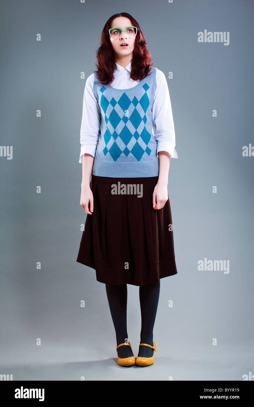 Geeky woman standing clueless and stunned - Stock Image
