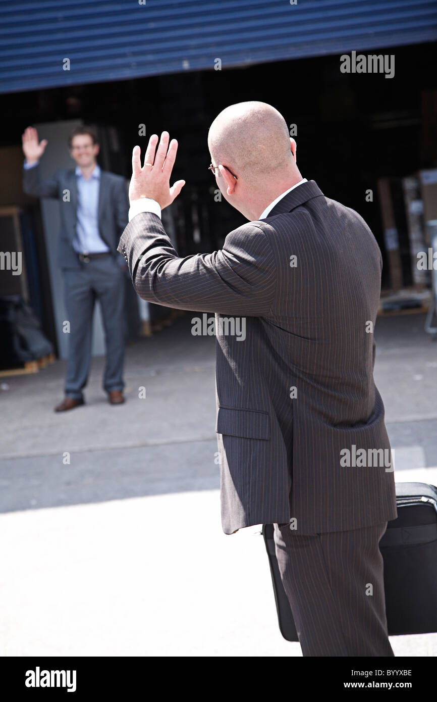 Businessman waving goodbye after meeting. - Stock Image