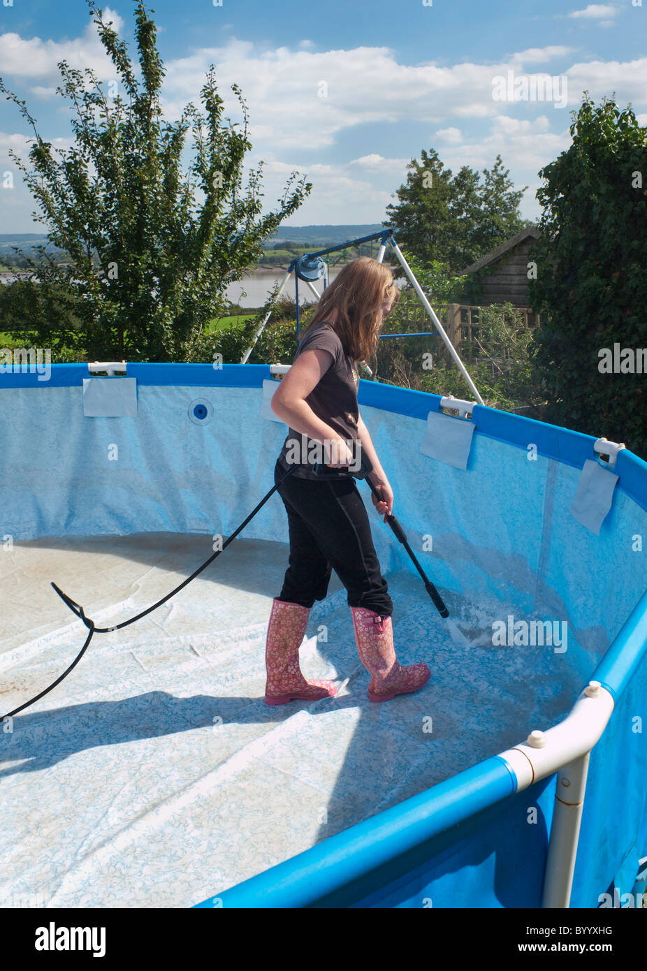 YOUNG GIRL CLEANING EMPTY COLLAPSIBLE SWIMMING POOL IN ...