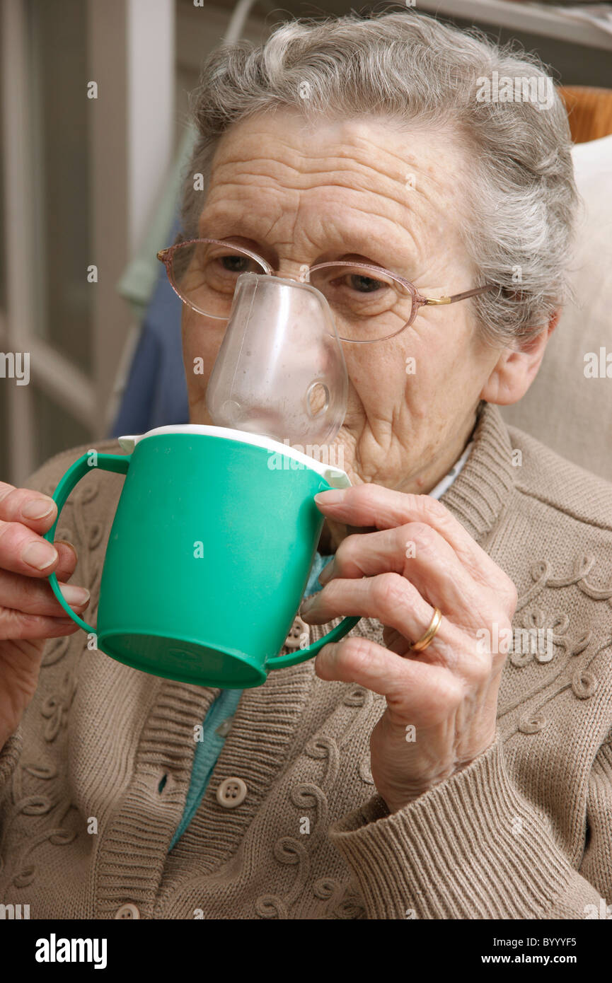 elderly woman using a steam inhaler inhaling a decongestant for colds & bronchitis - Stock Image