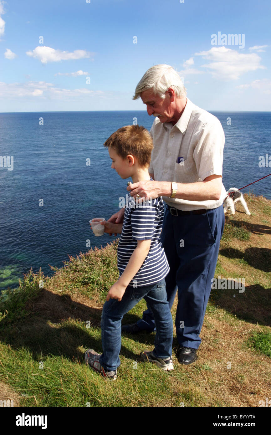Husband and grandson Spreading of ashes. - Stock Image