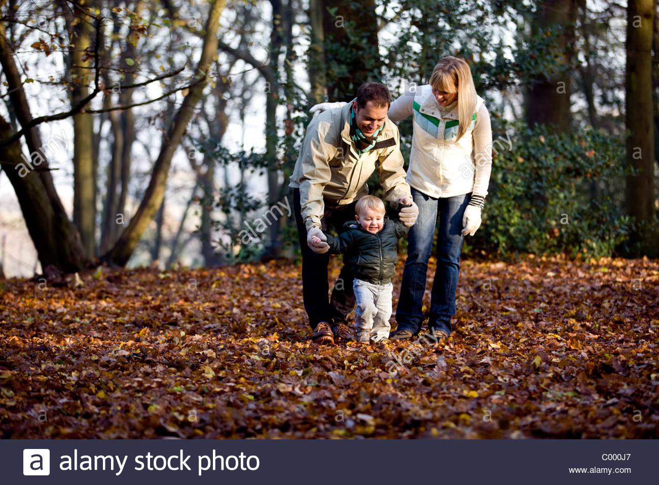 A young couple helping their son walk in the park - Stock Image