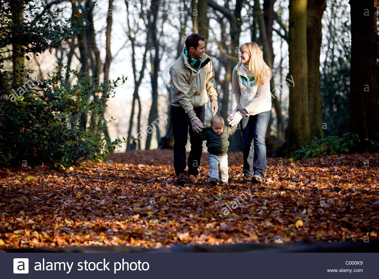 A young couple walking with their son in the park - Stock Image