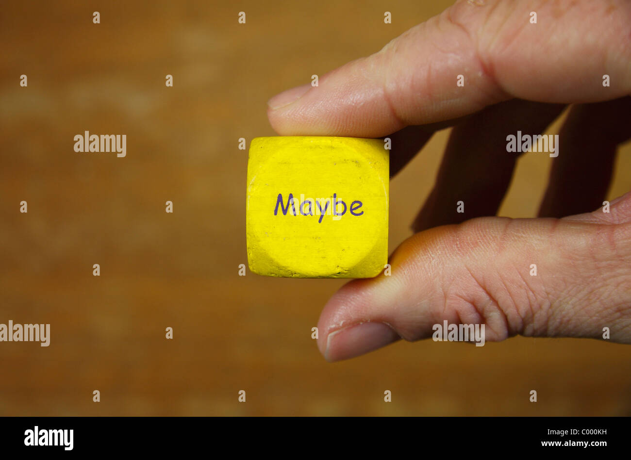 A man holding a yellow dice with the word 'MAYBE' inscribed upon it. - Stock Image