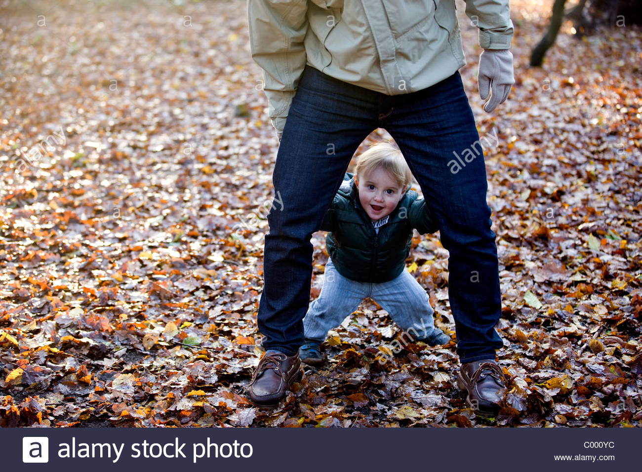 A young boy looking through his father's legs - Stock Image