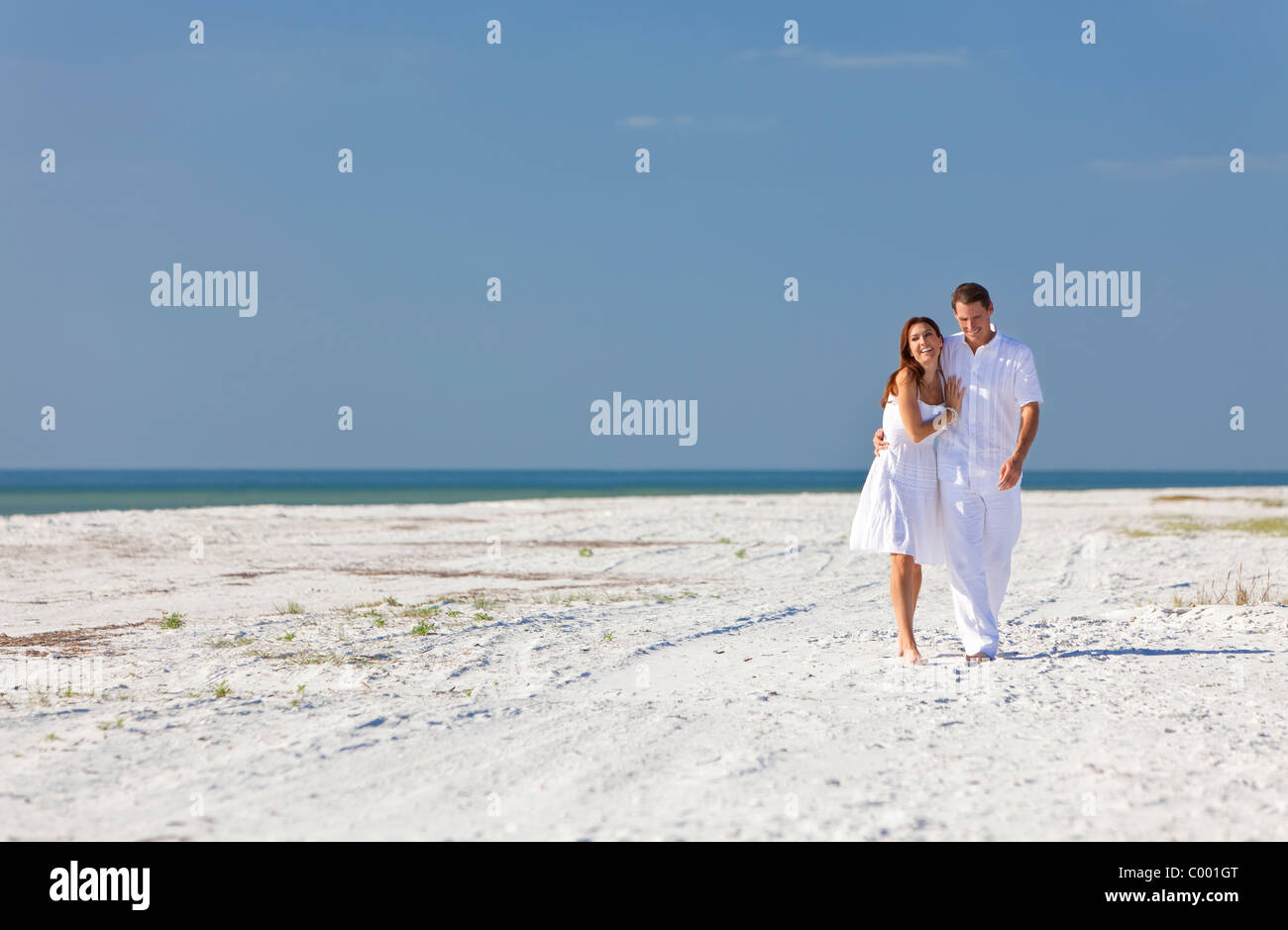 154b27baaa01 Man and woman romantic couple in white clothes walking and laughing  together on a deserted tropical beach with bright blue sky