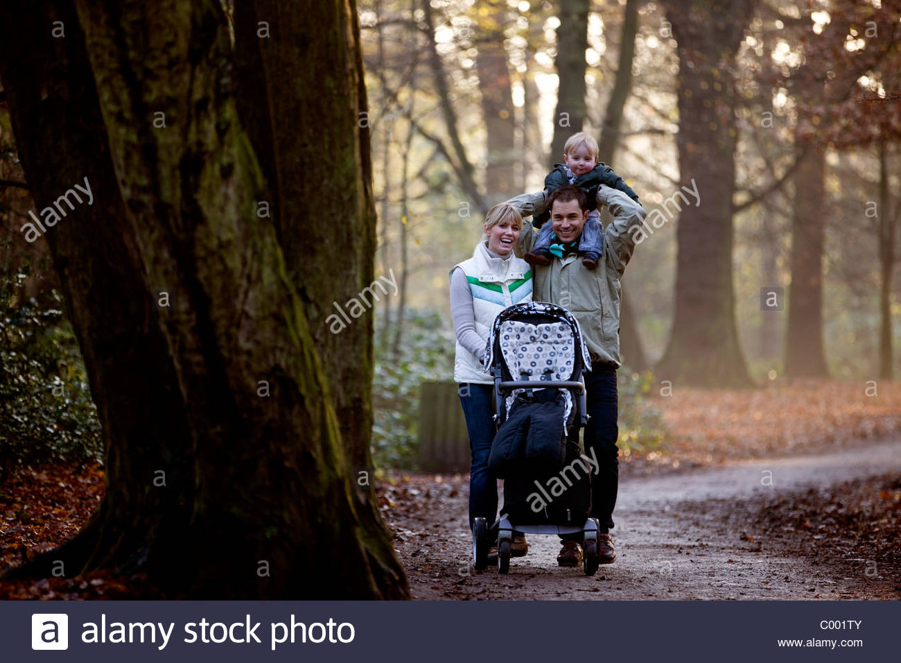 A family walking in the park, father carrying his son on his shoulders - Stock Image