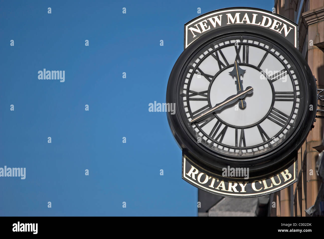 clock with roman numerals outside the rotary club of new malden, surrey, england - Stock Image