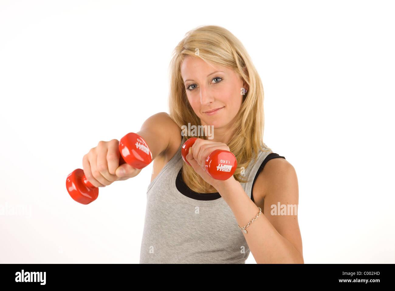 Junge blonde Frau in Sportkleidung mit Hanteln - Stock Image