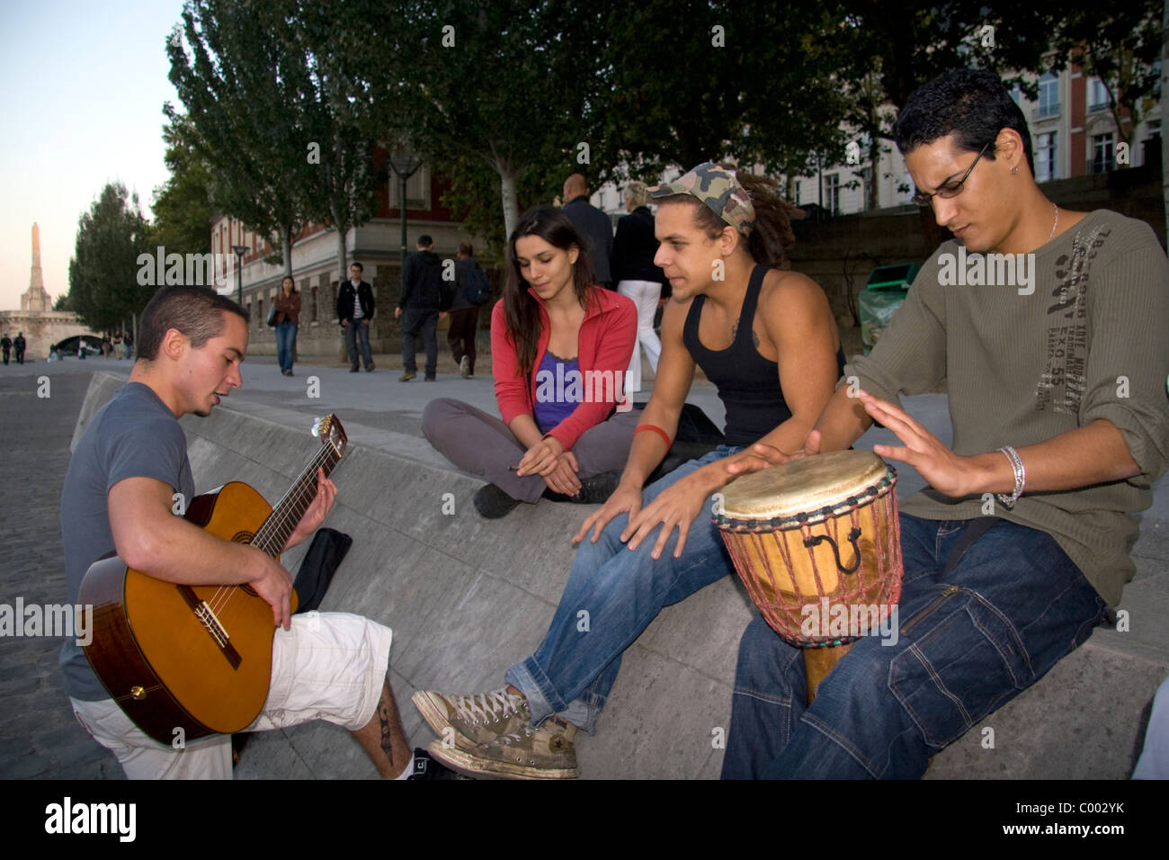 Young parisians play music along the River Seine in Paris, France. - Stock Image