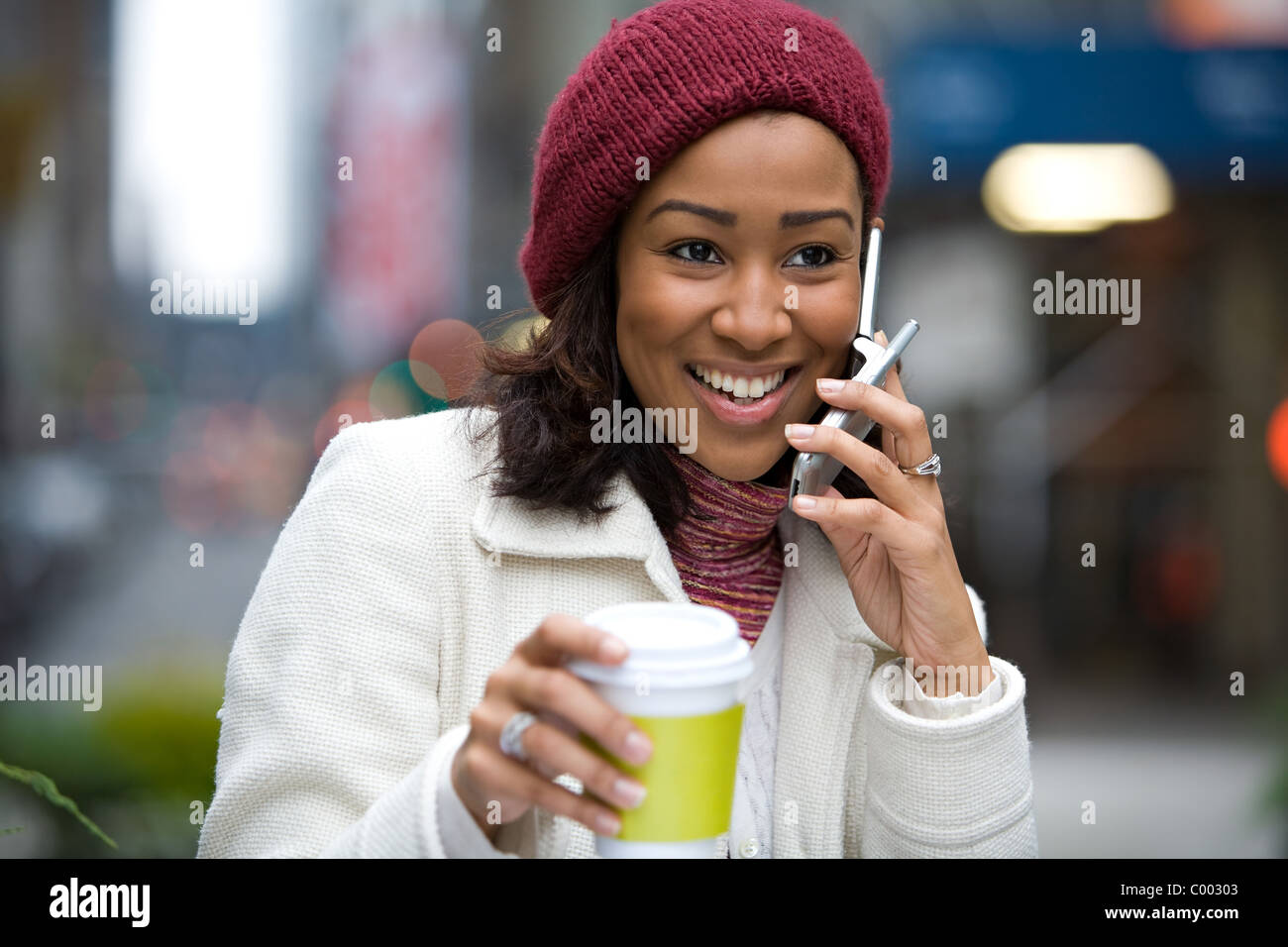 A modern business woman in the city talks on her cell phone while enjoying a cup of coffee. - Stock Image